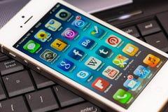 Pantalla iluminada de Apps del iPhone 5 en un teclado de ordenador Fotografía de archivo libre de regalías