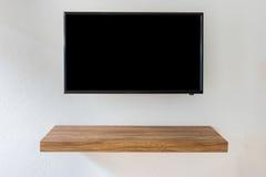 Pantalla negra de la televisión del LED TV en el fondo blanco de la pared con la tabla de madera moderna imagen de archivo