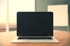 Pantalla negra en blanco del ordenador portátil en la tabla de madera en el backgr vacío de la oficina Fotos de archivo libres de regalías