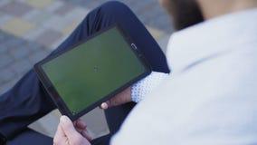 Pantalla táctil conmovedora de la mano masculina en la tableta 4K almacen de video