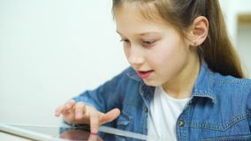 Pantalla táctil de la niña emocionada de la tableta mientras que juega a juegos en línea almacen de metraje de vídeo