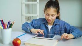 Pantalla táctil de la niña de la tableta mientras que juega a juegos en línea metrajes