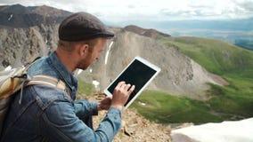 Pantalla táctil de las manos del hombre de la tableta digital en el fondo de montañas almacen de video