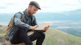 Pantalla táctil de las manos del hombre de la tableta digital en el fondo de montañas metrajes