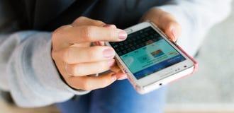 Pantalla táctil del dedo de la muchacha en el teléfono móvil Imagen de archivo