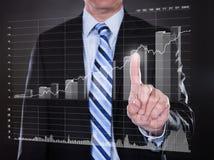 Pantalla transparente conmovedora del hombre de negocios con el gráfico de barra cada vez mayor Fotos de archivo libres de regalías