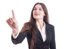 Pantalla transparente conmovedora joven de la mujer de negocios con el índice fing Foto de archivo libre de regalías