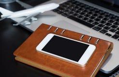 Pantalla vacía del smartphone en la oficina del cuaderno para el concepto del viaje de negocios fotos de archivo libres de regalías