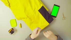 Pantalla verde Manos de los pantalones de costura de la mujer mayor metrajes