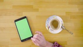 Pantalla verde Manos femeninas que enrollan una tableta almacen de video