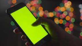 Pantalla verde, movimiento en sentido vertical femenino de la mano a través de la pantalla de un smartphone