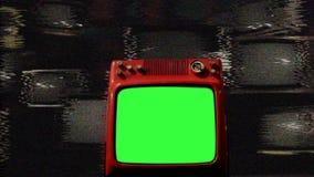 Pantalla vieja del verde del rojo TV en el medio de muchas TV Mala señal