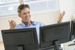 Pantallas múltiples de Gesturing While Using del comerciante feliz en el escritorio Imagenes de archivo