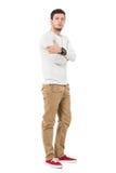 Pantalon beige de port debout d'homme sérieux avec les mains croisées regardant l'appareil-photo Photos stock
