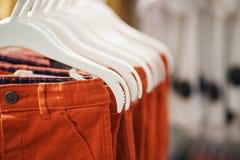 Pantalon pour des garçons sur un plan rapproché de cintre photo stock