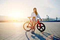 Pantalones cortos atractivos de la chica joven hermosa que montan su bicicleta en el embarcadero del puerto Foto de archivo libre de regalías