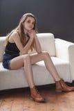 Pantalones cortos de los vaqueros de la muchacha que llevan que se sientan en el sofá Fotografía de archivo