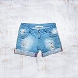 Pantalones cortos de los vaqueros en el fondo de madera Foto de archivo libre de regalías
