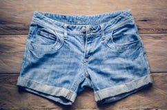 Pantalones cortos de los vaqueros en el piso de madera Fotos de archivo