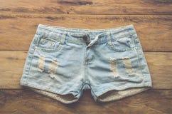 Pantalones cortos de los vaqueros en el piso de madera Foto de archivo libre de regalías