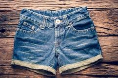 Pantalones cortos de los vaqueros en el piso de madera Fotografía de archivo