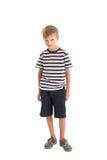 Pantalones cortos que llevan del muchacho y una camiseta rayada Fotografía de archivo