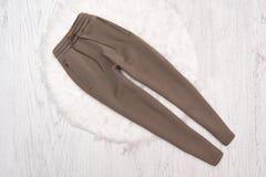Pantalones de Brown con las cremalleras en un fondo de madera fashionable Imagen de archivo