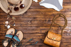 Pantalones de la natación, sombrero de paja, gafas de sol, sandalias y bolso en la tabla Imagenes de archivo