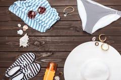 Pantalones de la natación, zapatos, sombrero de paja, gafas de sol y crema del sol en la tabla Foto de archivo