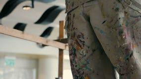 Pantalones sucios del pintor con muchas marcas coloridas de la pintura metrajes