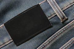 Pantalones vaqueros con la escritura de la etiqueta negra en blanco Imágenes de archivo libres de regalías