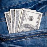 Pantalones vaqueros con los dólares americanos en su bolsillo Imágenes de archivo libres de regalías