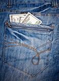 Pantalones vaqueros con los dólares americanos en su bolsillo Fotografía de archivo