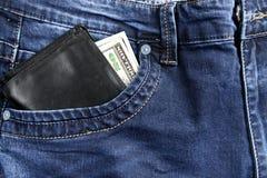 Pantalones vaqueros con los dólares en el bolsillo Foto de archivo