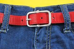Pantalones vaqueros de las mujeres con la correa de cuero roja Fotografía de archivo libre de regalías