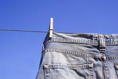 Pantalones vaqueros enclavijados a la línea de la colada Foto de archivo libre de regalías