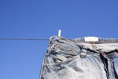 Pantalones vaqueros enclavijados a la línea de la colada Fotos de archivo