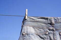Pantalones vaqueros enclavijados a la línea de la colada Foto de archivo