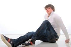 Pantalones vaqueros Mann joven que se sienta en el suelo blanco. Foto de archivo libre de regalías