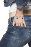Pantalones vaqueros que desgastan de la mujer joven y pulsera de plata Imágenes de archivo libres de regalías