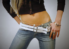 Pantalones vaqueros que desgastan y bijouterie del vientre apto de la mujer Imágenes de archivo libres de regalías