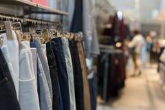 Pantalones y vaqueros en los estantes en tienda de ropa fotografía de archivo