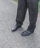 Pantalones y zapatos de los hombres Piernas de hombres de negocios hombre de negocios en negro Imágenes de archivo libres de regalías