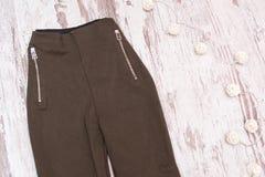 Pantaloni di Brown con le chiusure lampo su un fondo di legno fashionable Fotografia Stock