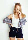 Pantaloni a vita bassa abbastanza biondi della ragazza dei giovani che posano frendly contro la parete bianca del fondo, donna so Immagine Stock