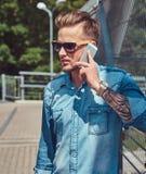 Pantaloni a vita bassa alla moda bei con taglio di capelli alla moda in occhiali da sole che parlano dal telefono mentre stando s Fotografie Stock