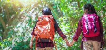 Pantaloni a vita bassa asiatici delle coppie che fanno un'escursione sull'avventura selvaggia di festa della montagna in autunno  immagine stock