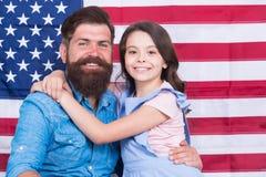 Pantaloni a vita bassa barbuti dell'americano del padre e piccola figlia sveglia con la bandiera di U.S.A. Diritto fondamentale d fotografia stock libera da diritti