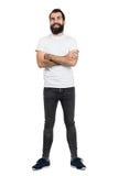 Pantaloni a vita bassa barbuti positivi felici in maglietta bianca e jeans stretti con le armi attraversate Fotografia Stock