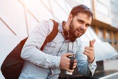 Pantaloni a vita bassa barbuti sorridenti moderni con lo zaino nero, le cuffie sul collo e la termo tazza con caffè a disposizion immagine stock libera da diritti